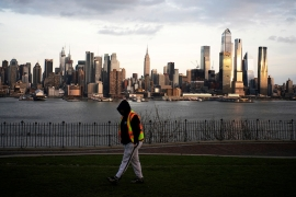 The Empire State Building and the skyline of New York are seen while a man walks around a local park in Weehawken, New Jersey, as the coronavirus outbreak continues in New York [Eduardo Munoz/Reuters]