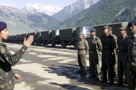 An Indian female military officer gives instructions to a group of army truck drivers beside a queue of trucks   May 13, 2002 [Fayaz Kabli/Reuters]