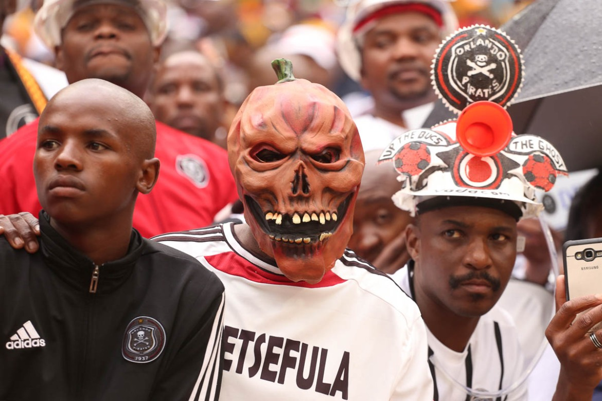 Creative masks and embellished hats are worn by Orlando Pirates fans to display their allegiance and try to intimidate the opposing team. [Antony Kaminju/Al Jazeera]