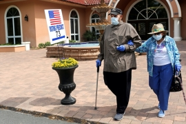 Voters wearing face masks to protect themselves from COVID-19 cast their ballots in the Democratic primary in The Villages, Florida, US, March 17, 2020 [Yana Paskova/Reuters]