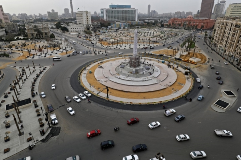 Cars drive in the Egyptian capital Cairo's Tahrir square on Wednesday, shortly before the first day of a two-week curfew imposed to contain the spread of coronavirus [Khaled Desouki/AFP]