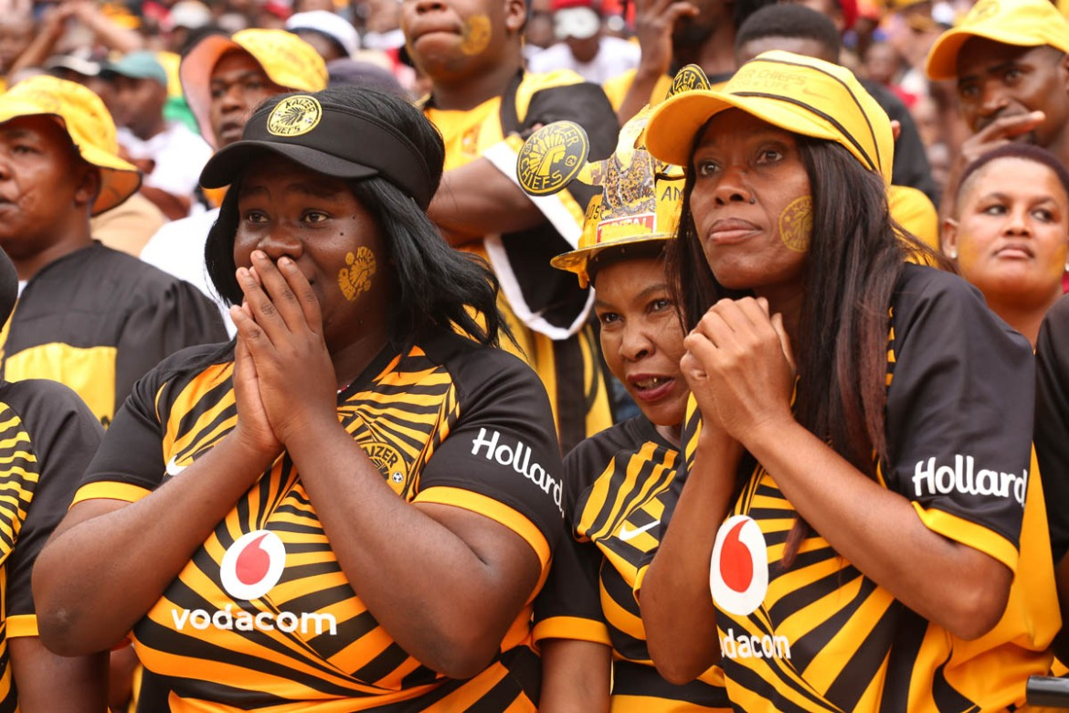 Kaizer Chiefs fans react to a missed opportunity to score. Some supporters dress elaborately, while others take a simpler approach. But all proudly display their team's colours - black and gold for the Chiefs, and black and white for the Pirates. [Antony Kaminju/Al Jazeera]