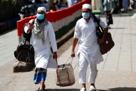 Men wearing protective masks carry their belongings at Nizamuddin in New Delhi amid concerns over the spread of the coronavirus [Adnan Abidi/Reuters]