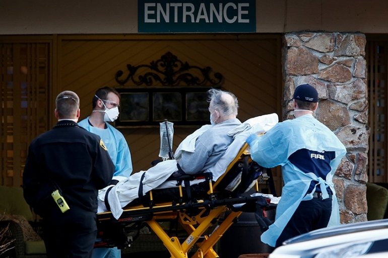 Medics wheel out a person on a stretcher from the Life Care Center of Kirkland, a long-term care facility linked to several confirmed coronavirus cases, in Washington state [Lindsey Wasson/Reuters]