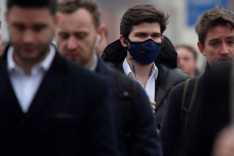 Workers, some wearing protective face masks, cross London Bridge during the morning rush hour in London, the United Kingdom, where banks are readying out-of-town offices and isolating some teams to ensure they can keep trading if coronavirus spreads [Toby Melville/Reuters]
