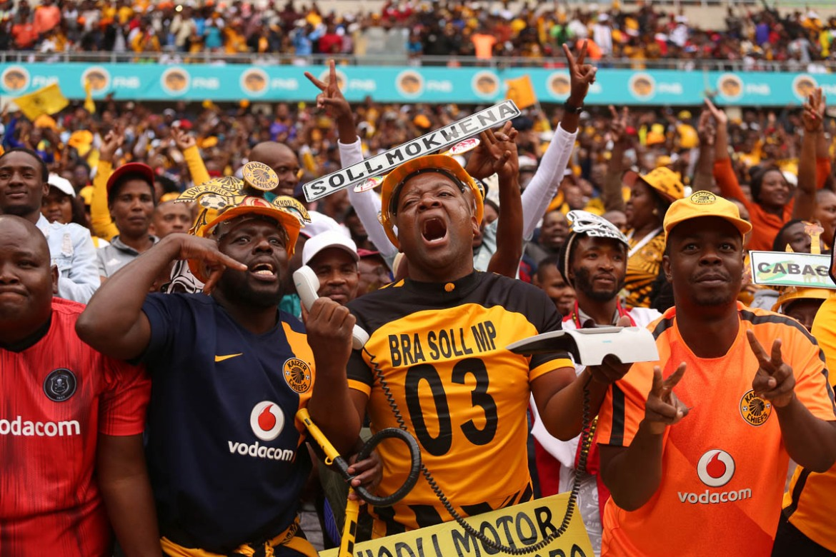 "Kaizer Chiefs fans react after one of the club's strikers fails to score a goal. One supporter carries a phone, while his friend gestures beside him, as if they are ""calling"" the coach to tell him to make a change. [Antony Kaminju/Al Jazeera]"