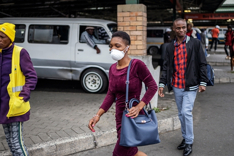 People in Johannesburg have started wearing masks as preventive measure against the virus [Michele Spatari/AFP]