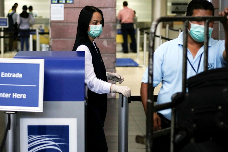 Airline employees wear protective masks, following the first cases of coronavirus in Honduras, at the Toncontin International airport in Tegucigalpa, Honduras [Jorge Cabrera/Reuters]