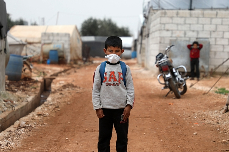 A Syrian boy poses for a picture during an awareness workshop on coronavirus at a camp for displaced people in Atme town in Syria's northwestern Idlib province [Aaref Watad/AFP]