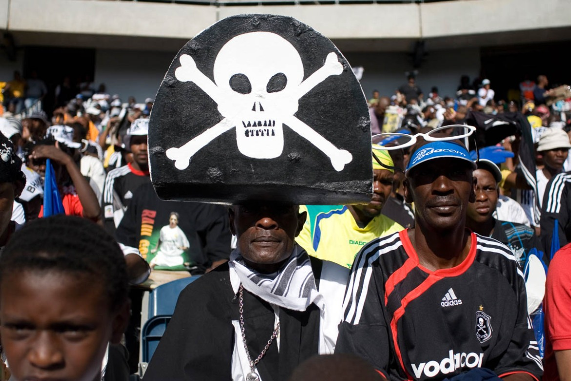 "Kenneth Metiba - who prefers to be called ""Long John Silver"" - is a die-hard fan of the Orlando Pirates. Now in his 60s, he has been a Pirates supporter since he was a teenager. He immerses himself in pirate regalia - dressing as one, and collecting paraphernalia associated with pirates to match the ideals of his favorite club, the Buccaneers. [Antony Kaminju/Al Jazeera]"