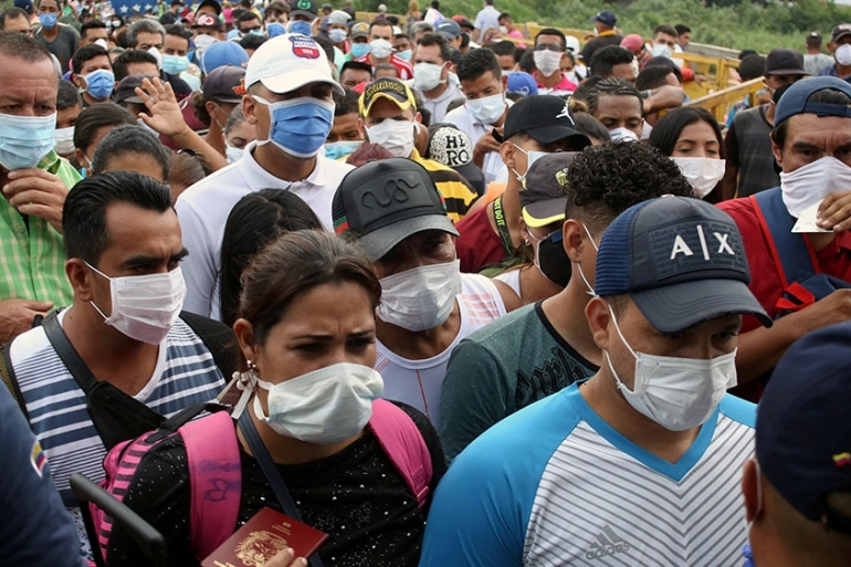 People wearing protective face masks line up to cross the border between Colombia and Venezuela at the Simon Bolivar international bridge, after the WHO declared the outbreak a pandemic, in Cucuta, Colombia  [Carlos Eduardo Ramirez/Reuters]