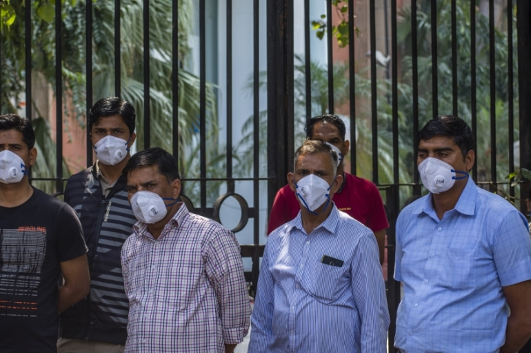People wear protective masks during a one-day nationwide curfew imposed as a preventive measure against COVID-19 on Sunday [Yawar Nazir/Getty Images]