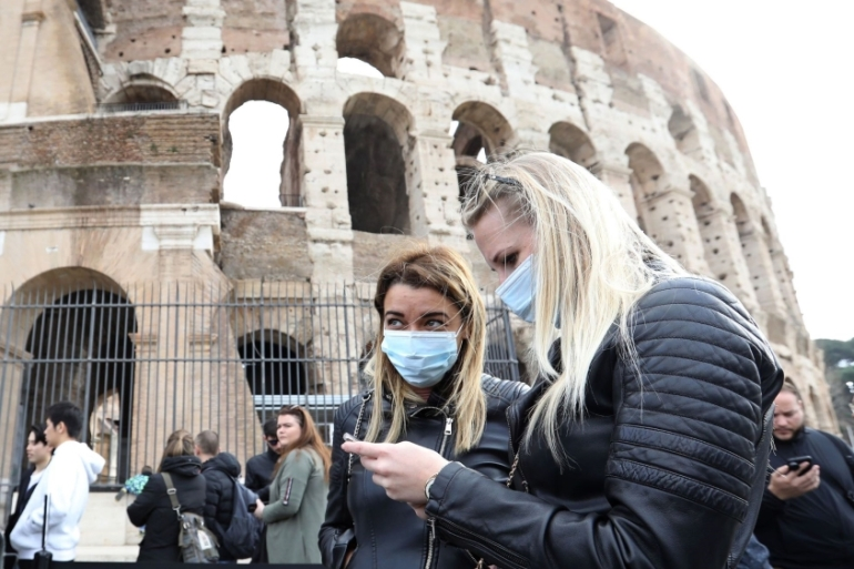 Visitors wearing protective face masks queue to enter the Colosseum in Rome [File: Alessia Pierdomenico/Bloomberg]