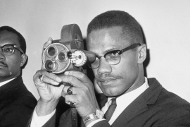 Malcolm X is shown with his 16mm Bell and Howell motion picture camera at JFK International Airport on July 9, 1964, before his departure for Egypt [Matty Zimmerman/AP]