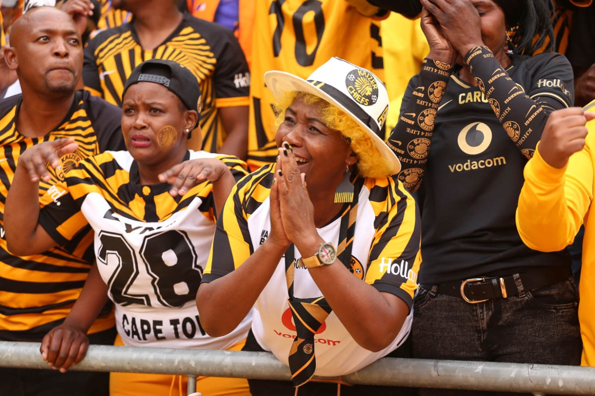 Female fans of the Kaizer Chiefs plea for a good game as they cheer on their team. [Antony Kaminju/Al Jazeera]
