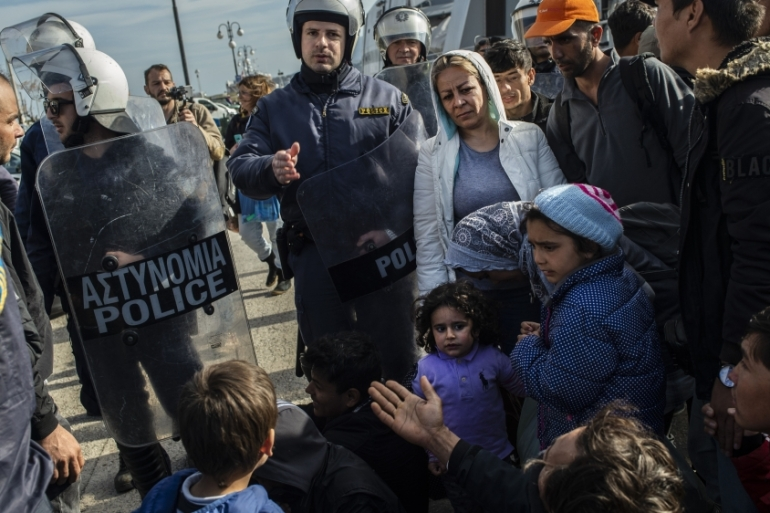 Riots police push back refugees and migrants outside the port of Lesbos, on March 3, 2020, amid a migration surge from neighbouring Turkey [Angelos Tzortzinis/AFP]