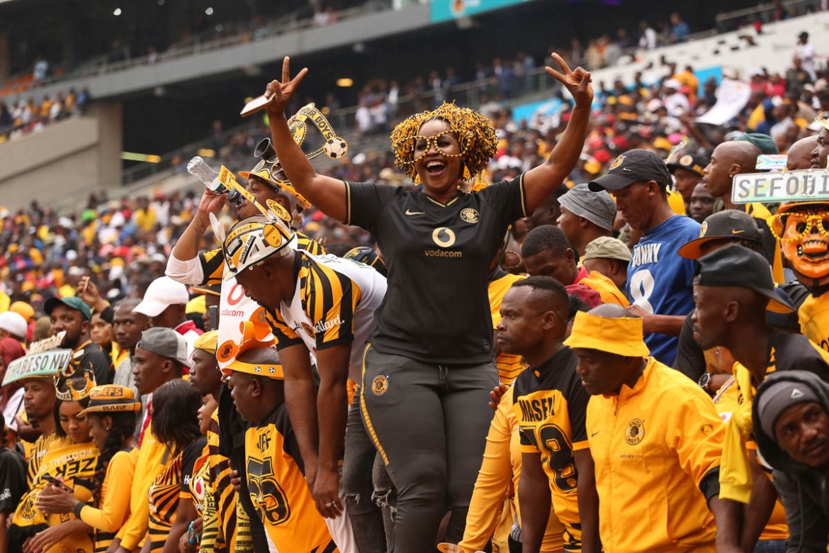 Kaizer Chiefs fan Nelly Kubai celebrates after her team scores the winning goal against their rivals the Orlando Pirates. She has been a Chiefs supporter for more than 20 years and on the day of the Derby she travelled from Pretoria, 30km from Johannesburg, to support her team. [Antony Kaminju/Al Jazeera]