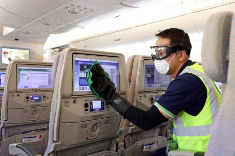 A member of cleaning staff disinfects a seat screen of an Emirates Airbus A380 before the carrier said it would suspend almost all passenger flights due to the coronavirus outbreak [File: Emirates Airline via Reuters]