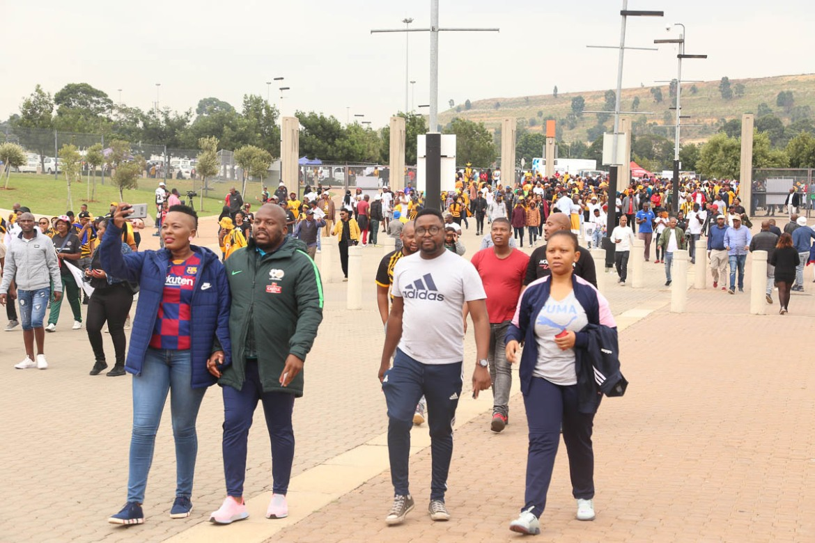 Football enthusiasts make their way to the FNB Stadium for the 50th anniversary of the Soweto Derby. The 90,000 seater stadium was filled to capacity for the game on February 29, 2020. [Antony Kaminju/Al Jazeera]