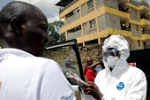 A health worker dressed in a protective suit prepares to disinfect the residence where Kenya's first confirmed coronavirus patient was staying, in Rongai, Kenya, March 14, 2020 [Baz Ratner/Reuters]