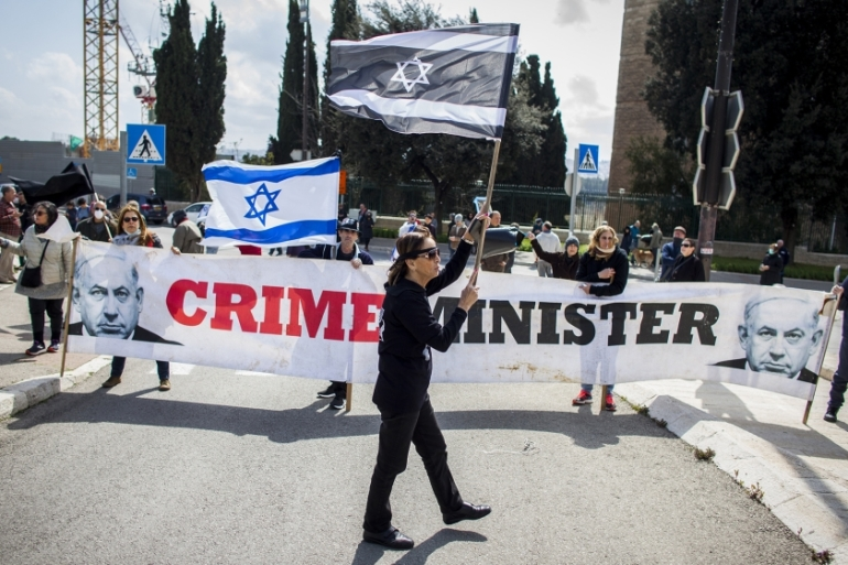 People wave Israeli flags and carry a banner reading 'crime minister' during a protest outside the Israeli parliament in Jerusalem [Eyal Warshavsky/AP]