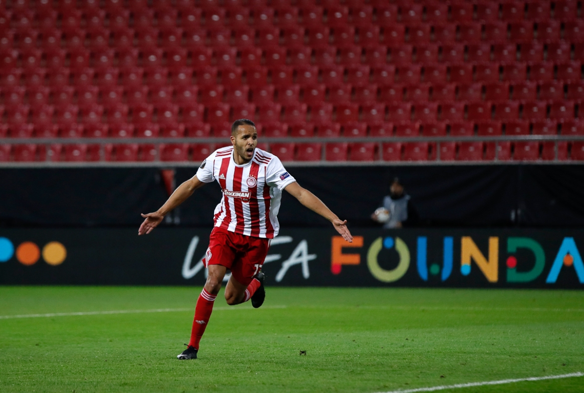 Olympiakos' Youssef El-Arabi celebrates after scoring his side's opening goal during the Europa League match against Wolverhampton Wanderers at the Karaiskakis Stadium, played in an empty stadium. [Thanassis Stavrakis/AP Photo]