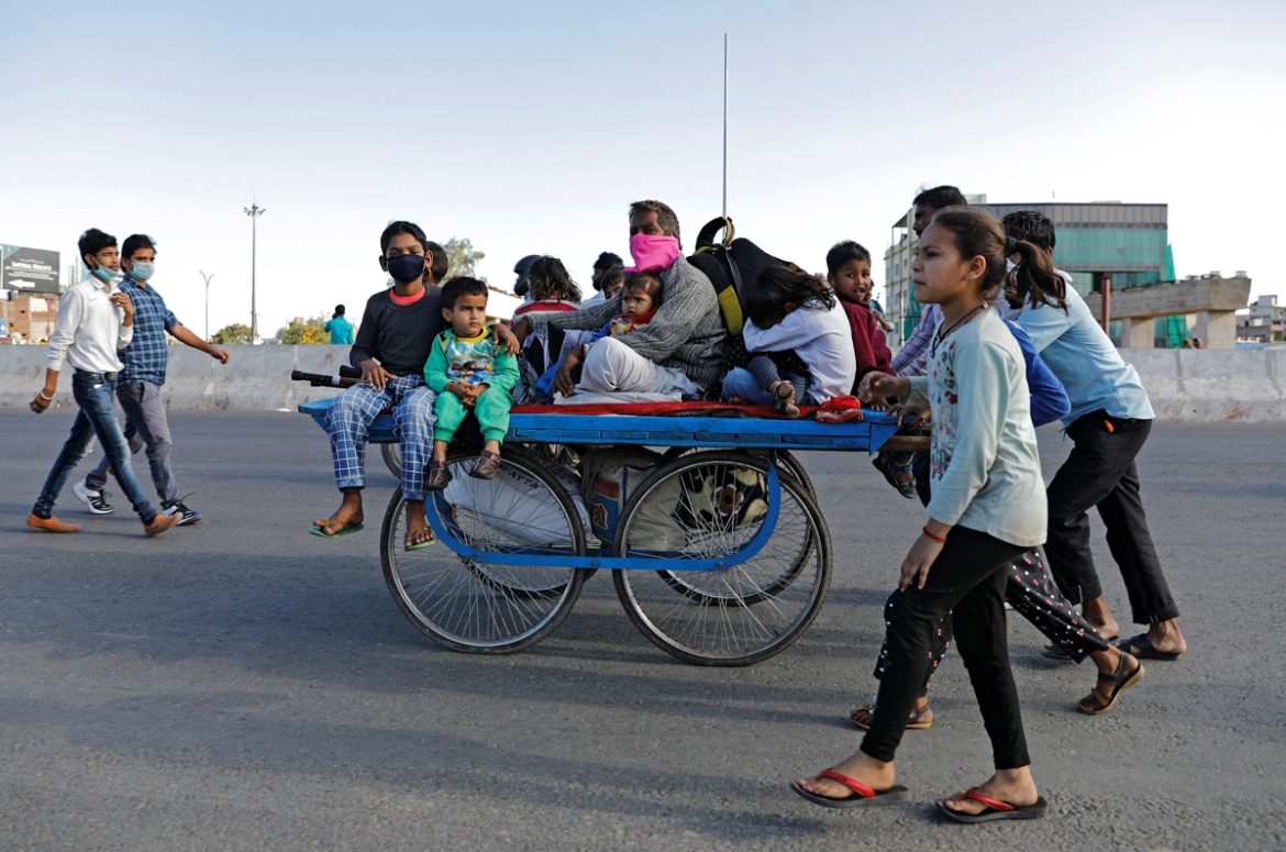 A migrant worker rides a cart with his family on a highway as they return to their villages, during the 21-day nationwide lockdown. [Adnan Abidi/Reuters]