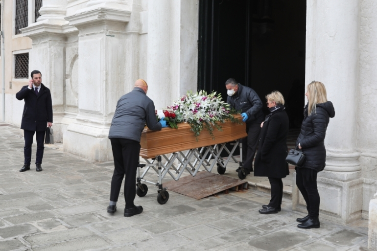 A coffin is taken out of the hospital in the presence of two relatives and a funeral home employee in Venice, Italy [Marco Di Lauro/Getty Images]