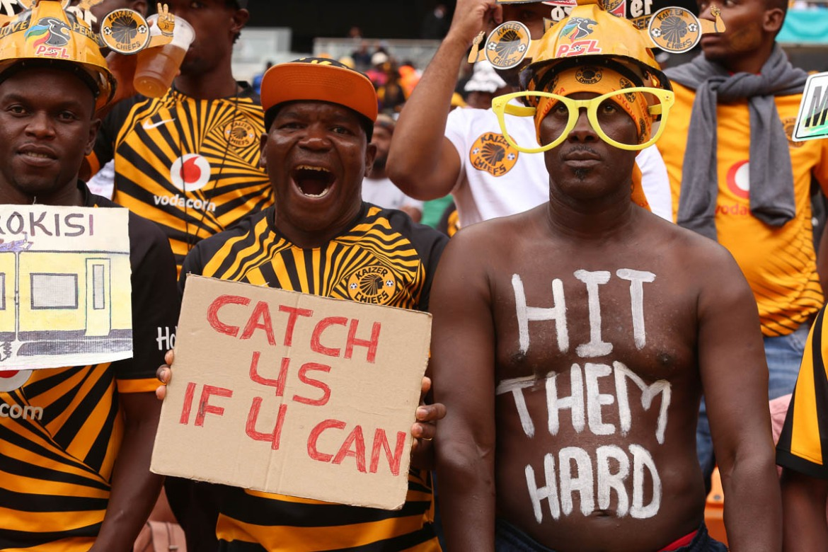 "Kaizer Chiefs fan Bolelang Gape has painted a message for his team on his body: ""Hit them hard"", referring to the defeat he foresees Orlando Pirates suffering at the hands of his team. Signage and body painting are other ways opposing fans mock and goad each other. [Antony Kaminju/Al Jazeera]"