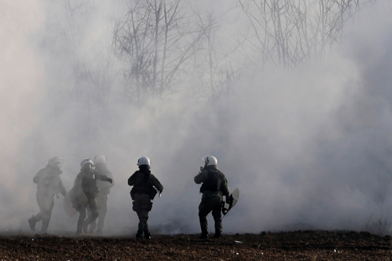 Greek riot police officers walk amid clouds of tear gas near the Turkish-Greek border [Reuters]