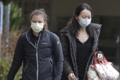Two women wearing masks walk away from the Life Care Center in Kirkland, Washington on Monday, March 2, 2020 [Ted S. Warren/The Associated Press]