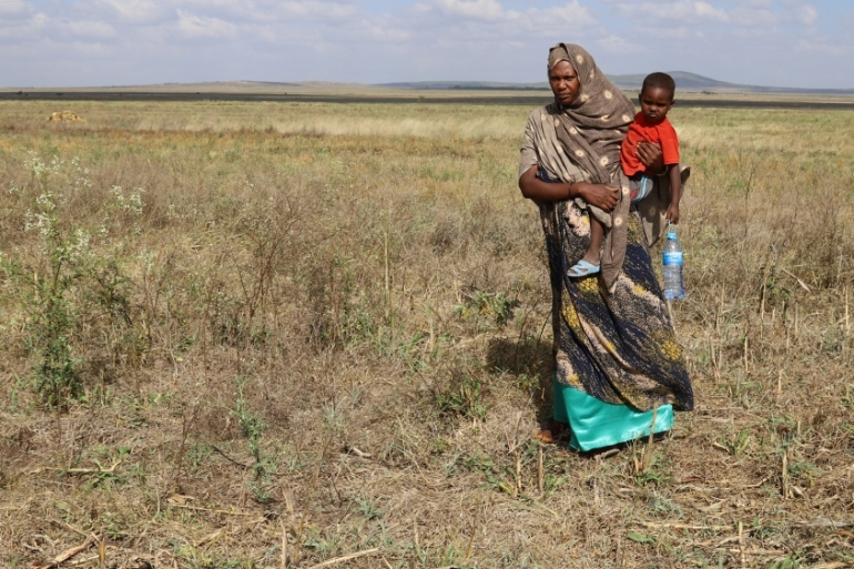 Asha Khalif Ali, 35, an internally displaced Ethiopian, carries her son in her wheat field that was damaged by heavy rains and desert locusts [File: Giulia Paravicini/Reuters]