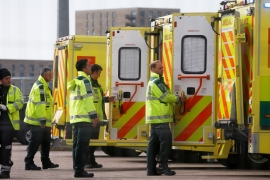 Paramedics and ambulances are seen outside the Excel Centre, London while it is being prepared to become the NHS Nightingale Hospital [Henry Nicholls/Reuters]