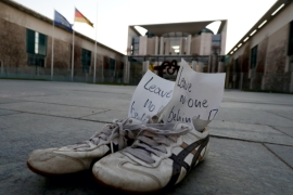 A pair of shoes with a note that says: 'Leave no one behind' inside seen during a demonstration to demand help for refugees in Berlin, Germany April 5, 2020 [Michele Tantussi/Reuters]