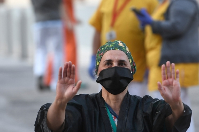 A healthcare worker acknowledges applause outside the Gregorio Maranon Hospital in Madrid on April 12, 2020 during a national lockdown to prevent the spread of the COVID-19 disease [Pierre-Philippe Marcou/AFP]