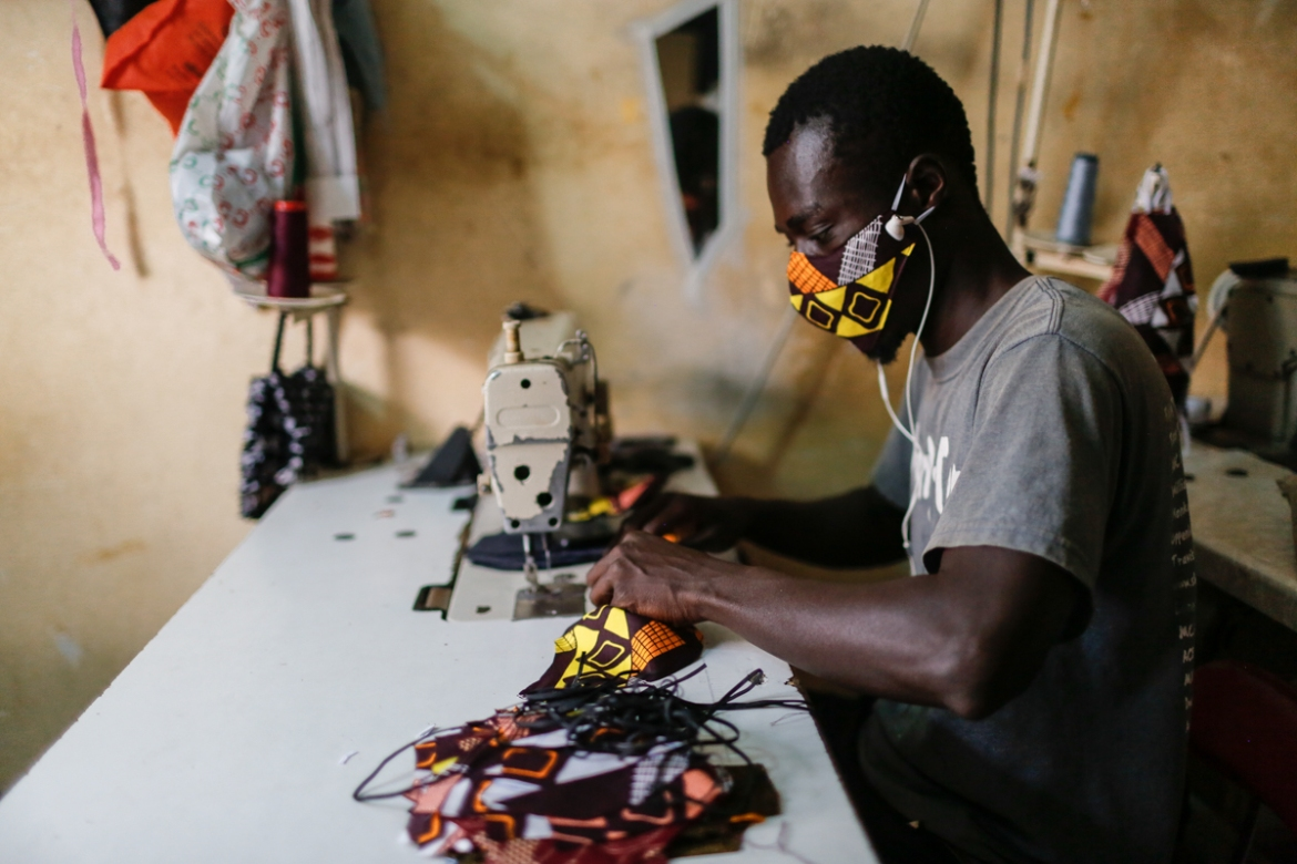 A tailor in a western Dakar neighbourhood, where a high number of coronavirus cases have been recorded, sews double-layered masks made from African print fabric. Although Dakar is not facing a shortage of medical-grade masks, colourful handmade masks, sold for one dollar, have proliferated in Dakar. [Maya Hautefeuille/Al Jazeera]