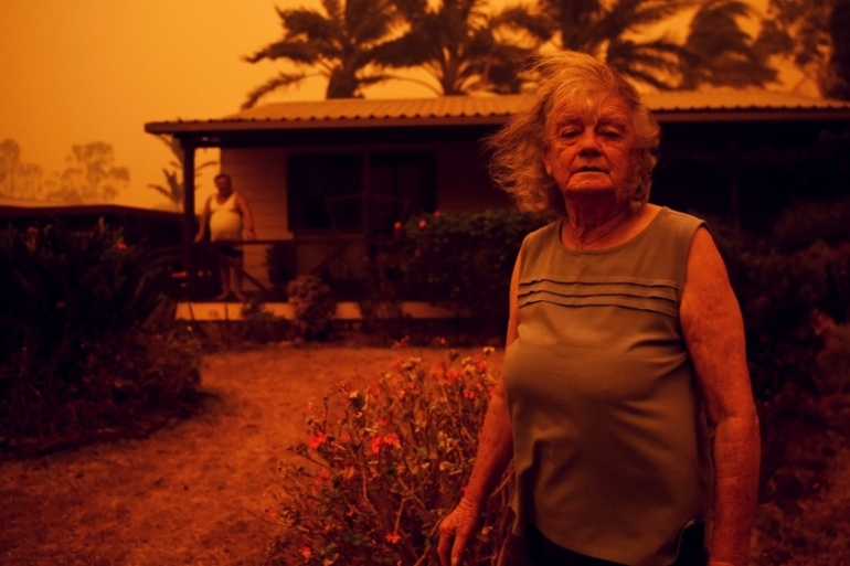 Nancy Allen and Brian Allen stand outside as high winds push smoke and ash from the Currowan Fire towards Nowra, New South Wales, Australia on January 4, 2020 [File: Tracey Nearmy/Reuters]