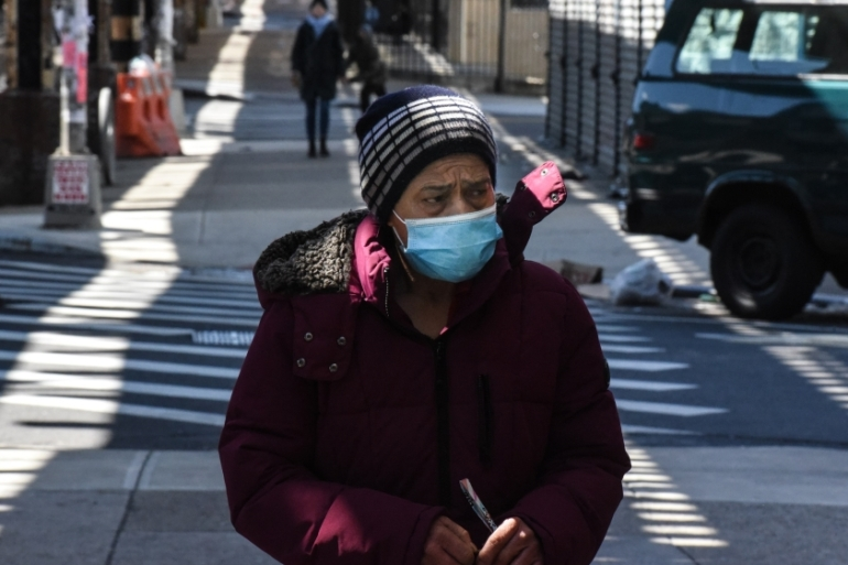 A person wearing a protective mask walks along Myrtle Avenue in the Bushwick neighbourhood of Brooklyn, in New York, the United States [Stephanie Keith/Getty Images/AFP]