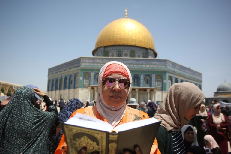 A Palestinian woman in headscarves and long robes seated on the floor of the Al-Aqsa mosque compound reading the Quran holy book [File: Anadolu]