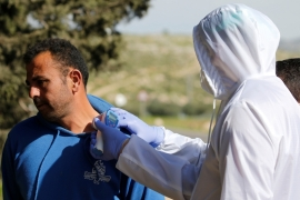 A medic checks the body temperature of a Palestinian worker returning from Israel [Mussa Qawasma/Reuters]