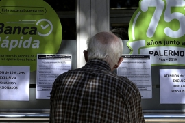 An elderly man waits outside a bank with signs advertising attention between 10 and 12 is exclusively for retired and pensioners during the outbreak of the new Coronavirus, COVID-19, in Buenos Aires, Argentina [Juan Mabromata/AFP]