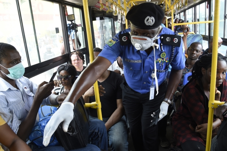 Lagos Commissioner of Police Hakeem Odumosu, centre, speaks to passengers to enforce social distancing in a bus as part of measures to curb the spread of coronavirus in Lagos, Nigeria [Pius Utomi/AFP]