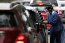A health worker tests people for coronavirus at a drive-thru testing facility in Monterrey [File: Daniel Becerril/Reuters]
