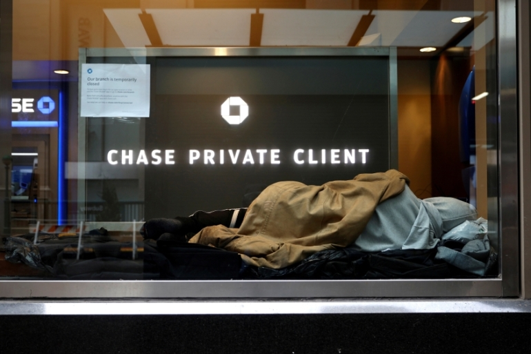 A homeless man sleeps in a closed Chase bank branch on Wall Street in the financial district in lower Manhattan during the coronavirus outbreak in NY, US, where the death toll from the pandemic is fast approaching 11,000 people [File: Mike Segar/Reuters]