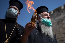 The annual Holy Fire ceremony took place behind closed doors in the Church of the Holy Sepulchre in Jerusalem's old city. The flame was then taken to Orthodox countries worldwide. [Ariel Schalit/AP Photo]