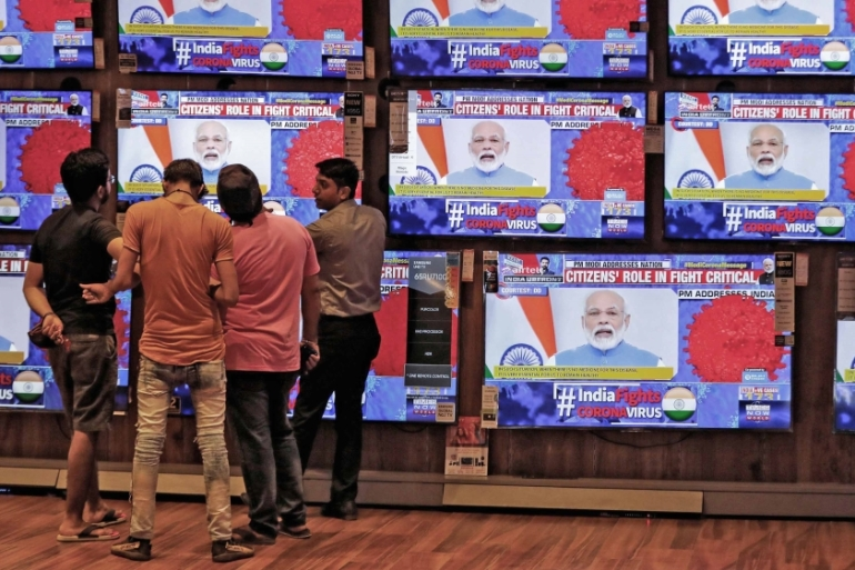 People watch Indian Prime Minister Narendra Modi address the nation amid concerns about the spread of coronavirus inside a showroom in Ahmedabad, India on March 19, 2020 [Reuters/Amit Dave]