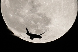 An airplane is silhouetted against the full Moon [File: Reuters]