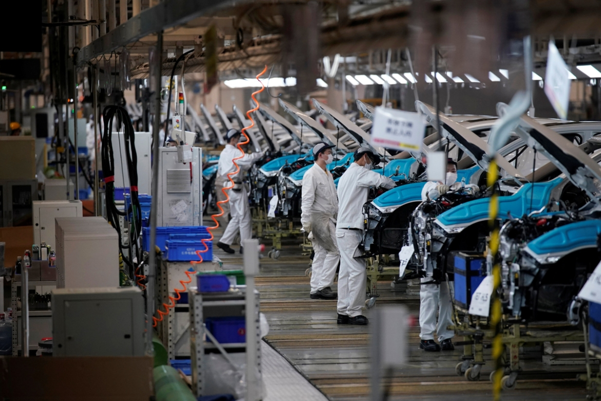 Employees work on a production line inside the Dongfeng Honda factory after lockdown measures in Wuhan were further eased. [Aly Song/Reuters]