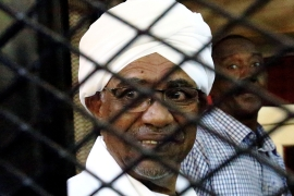 Sudan's former president Omar Hassan al-Bashir sits inside a cage at the courthouse where he is facing corruption charges, in Khartoum on September 28, 2019 [File: Mohamed Nureldin Abdallah/Reuters]