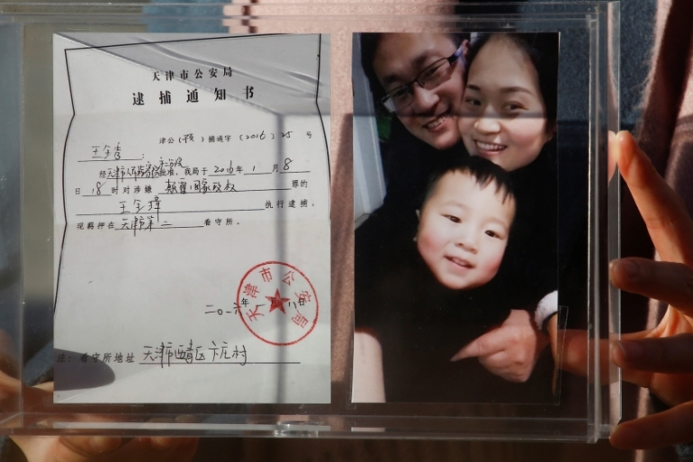 Li Wenzu, the wife of prominent Chinese rights lawyer Wang Quanzhang, holds a box with a family picture and the detention notice for her husband in Beijing [File: Thomas Peter/Reuters]